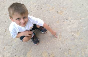 My son happy to have found one of the very clear tracks at the Red Gulch Dinosaur Tracksite, near Shell, WY.
